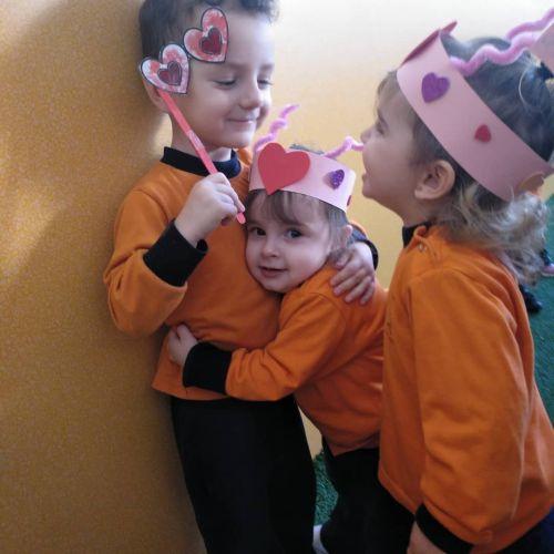 Niños disfrazados con coronas y antifaz caseros de corazones